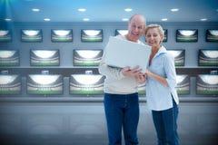 微笑对与膝上型计算机的照相机的成熟夫妇的综合图象 免版税库存图片