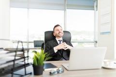 微笑对书桌的体贴的男性总经理 免版税库存照片