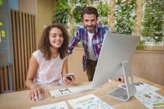 微笑对书桌的董事画象,当研究个人计算机时 库存照片