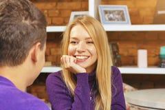 微笑对人的女孩坐在咖啡馆 首次会议日期 免版税库存图片