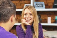 微笑对人的女孩坐在咖啡馆 首次会议日期 库存图片