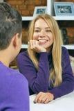微笑对人的女孩坐在咖啡馆 首次会议日期 库存照片