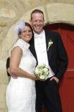微笑对他们的婚礼之日的愉快的新娘夫妇 免版税库存照片