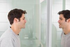 微笑对在卫生间镜子的自已的一个年轻人的侧视图 免版税库存照片