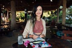 微笑对在夏天咖啡馆的木桌的画象美丽的深色的妇女 免版税库存图片