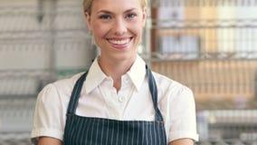 微笑对在她的杯形蛋糕旁边的照相机的愉快的服务器 股票录像