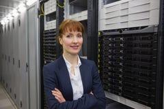 微笑对在服务器塔旁边的照相机的俏丽的技术员 免版税库存图片