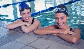 微笑对在游泳池的照相机的女性游泳者 免版税库存图片