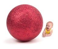 微笑对在白色的一件巨大的圣诞节装饰品的逗人喜爱的婴孩 免版税库存照片