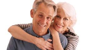 微笑对在白色背景的照相机的愉快的资深夫妇 库存图片