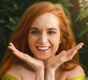 微笑对在绿色的照相机的快乐的红发女孩 免版税库存图片