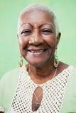 微笑对在绿色backgr的照相机的高级黑人妇女纵向  库存图片