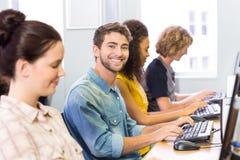 微笑对在计算机类的照相机的学生 库存图片