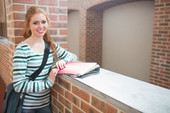 微笑对在走廊的照相机的红头发人学生 库存图片