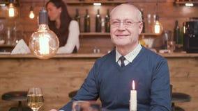 微笑对在酒吧的照相机的一个英俊的老人的画象 影视素材