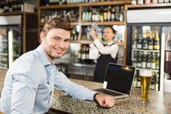 微笑对在酒吧的照相机的人 免版税库存照片