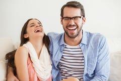 微笑对在长沙发的照相机的年轻夫妇 库存照片
