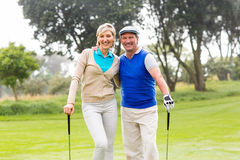 微笑对在高尔夫球区的照相机的打高尔夫球的夫妇 免版税库存照片