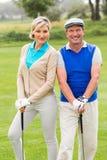 微笑对在高尔夫球区的照相机的打高尔夫球的夫妇 免版税图库摄影