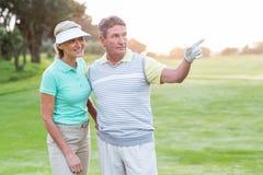 微笑对在高尔夫球区的照相机的打高尔夫球的夫妇 库存照片