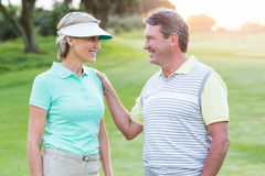 微笑对在高尔夫球区的照相机的打高尔夫球的夫妇 库存图片