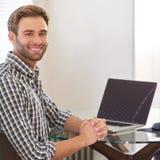 微笑对在他的肩膀的照相机的英俊的年轻成人人 免版税库存照片