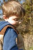 微笑对在他的胳膊的一只蚂蚱的年轻男孩 库存照片