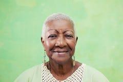 微笑对在绿色backgr的照相机的资深黑人妇女画象  图库摄影