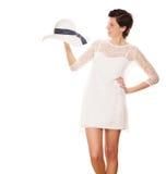 微笑对太阳帽子的妇女在她的手上 免版税库存图片