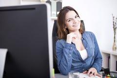 微笑对她的工作台的俏丽的办公室妇女 免版税图库摄影