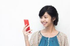 微笑对她的智能手机的美丽的亚裔女孩 免版税图库摄影