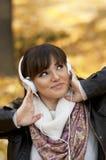 微笑对妇女的美好的听的音乐 免版税库存图片