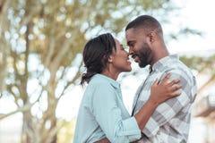 微笑对彼此的富感情的年轻非洲夫妇外面 库存照片