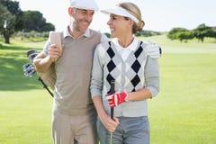 微笑对彼此的打高尔夫球的夫妇在高尔夫球区 免版税库存图片