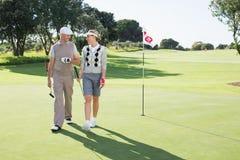 微笑对彼此的打高尔夫球的夫妇在高尔夫球区 图库摄影