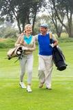 微笑对彼此的打高尔夫球的夫妇在高尔夫球区 免版税库存照片