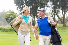 微笑对彼此的打高尔夫球的夫妇在高尔夫球区 免版税图库摄影