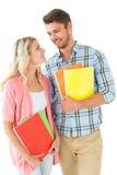 微笑对彼此的有吸引力的学生夫妇 库存图片