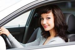 微笑对您的俏丽的妇女司机 免版税库存图片