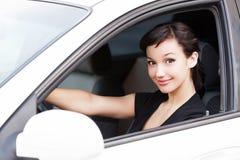 微笑对您的俏丽的妇女司机 库存照片