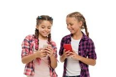 微笑对手机屏幕的女孩逗人喜爱的小孩子 他们喜欢互联网冲浪人脉 问题的年轻 库存图片