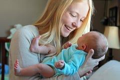 微笑对新出生的婴孩的年轻母亲在家庭托儿所 库存图片