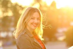 微笑对日落的一名愉快的妇女的画象 免版税库存照片