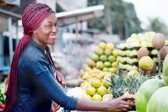 微笑对水果市场的少妇 图库摄影