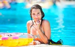 微笑对池的愉快的美丽的青少年的女孩 免版税库存照片
