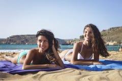 微笑对海滩的两个美丽的女孩 免版税库存图片