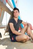 微笑对海滩的愉快的年轻人 免版税库存照片