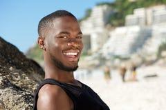 微笑对海滩的愉快的年轻人 免版税库存图片