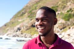 微笑对海滩的愉快的年轻非裔美国人的人 免版税图库摄影
