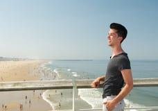 微笑对海滩的年轻人 免版税库存照片